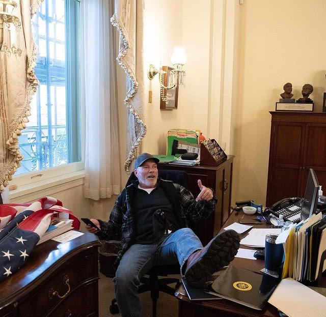 A rioter breaks into Speaker of the House Nancy Pelosi's office, and poses for a photo with his feet on her desk.
